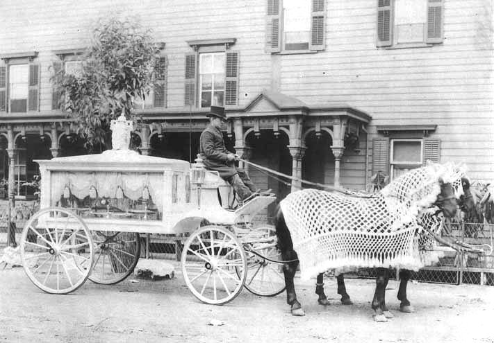 Horse-drawn_funeral_hearse_with_driver_outside_Neil_Regan_Funeral_Home_Scranton_PA_circa_1900